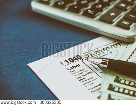 Tax Form 1040, Pen, Calculator And Dollars On A Blue Table. The Concept Of Business Taxation And Bus