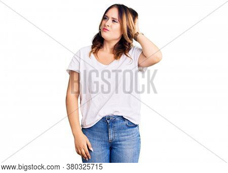 Young beautiful caucasian woman wearing casual white tshirt confuse and wondering about question. uncertain with doubt, thinking with hand on head. pensive concept.