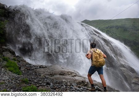 Waterfall Landscape And Male Traveler Enjoying Waterfall View.