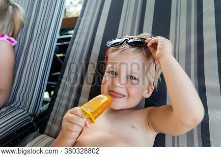 Two Cute Adorable Caucasian Blond Little Siblings Enjoy Having Fun Relaxing And Eat Fruit Popsicle I