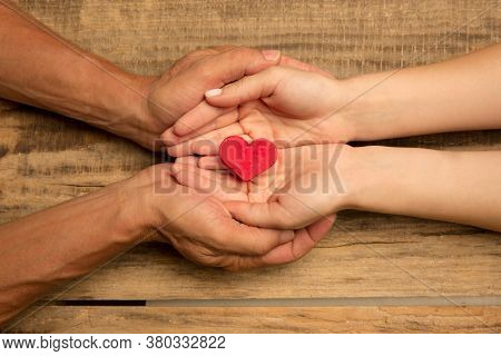 Human Hands Holding, Giving Heart Isolated On Wooden Background. Concept Of Emotions, Feelings, Char