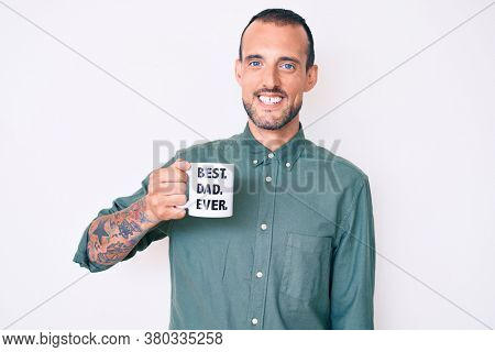 Young handsome man with tattoo drinking mug of coffe with best dad ever message looking positive and happy standing and smiling with a confident smile showing teeth