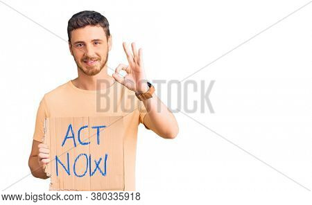 Handsome young man with bear holding act now banner doing ok sign with fingers, smiling friendly gesturing excellent symbol