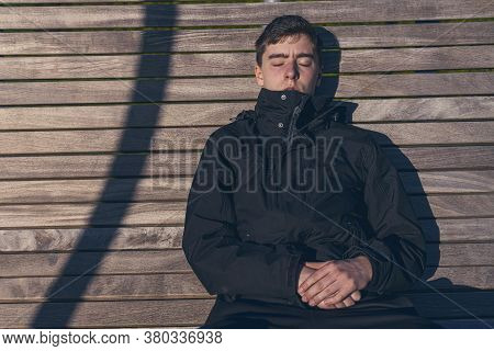 Young Man Sitting On A Bench In The Sun With His Eyes Closed
