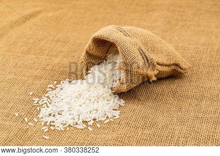 Jasmine Rice Flow From A Sack To The Floor Covered With Sackcloth