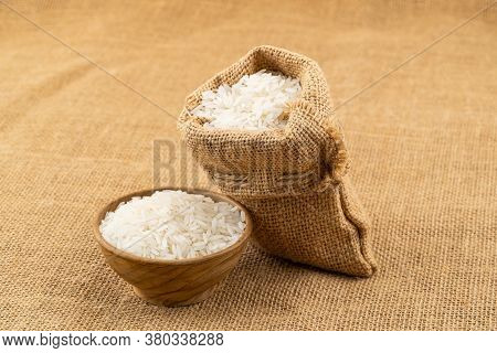 Jasmine Rice In A Wooden Bowl And In A Sack On Sackcloth.