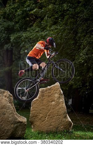 Front View Of Man Holding A Bicycle Handlebar And Doing A Stunt Over Stones. Athlete Trying To Land