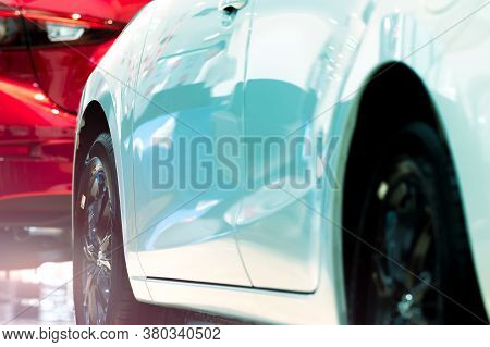 Selective Focus Of New Shiny White Car Parked In Modern Showroom. Car Dealershep Concept. Car For Re