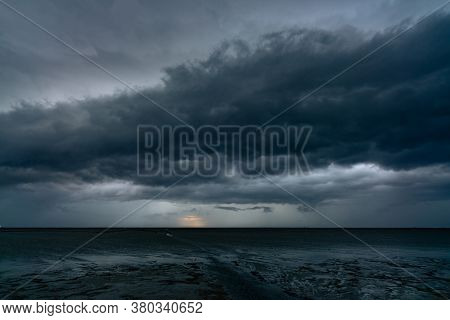 Landscape View Of Sea At Tide And Silhouette Dark Dramatic Sunset Sky And Clouds In The Evening. Sun