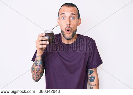 Young handsome man with tattoo drinking mate infusion scared and amazed with open mouth for surprise, disbelief face