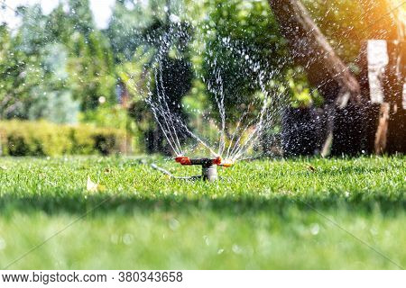 Landscape Automatic Garden Watering System With Different Rotating Sprinklers Installed On Turf. Lan
