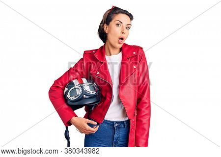 Young beautiful woman holding motorcycle helmet scared and amazed with open mouth for surprise, disbelief face