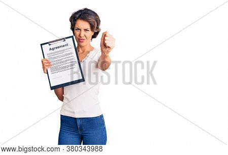 Young beautiful woman holding clipboard with agreement document annoyed and frustrated shouting with anger, yelling crazy with anger and hand raised