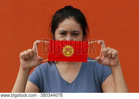 A Woman With Kyrgyzstan Flag On Hygienic Mask In Her Hand And Lifted Up The Front Face On Orange Col