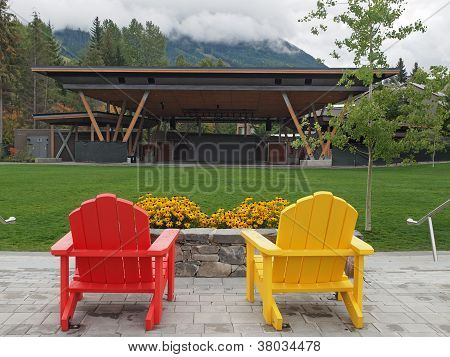Wooden  brightly painted Adirondak chairs set in mountainpark poster