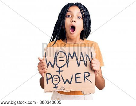 Cute african american girl holding woman power banner scared and amazed with open mouth for surprise, disbelief face