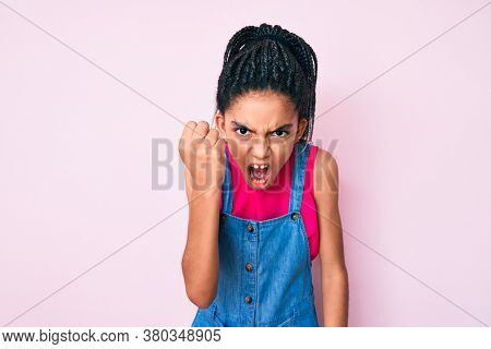 Young african american girl child with braids wearing casual clothes over pink background angry and mad raising fist frustrated and furious while shouting with anger. rage and aggressive concept.