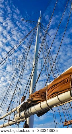 Sailing Gear. In The Blue Sky, A Vertical Mast, Yards, Cables. The Beige Sail Is Rolled And Reinforc