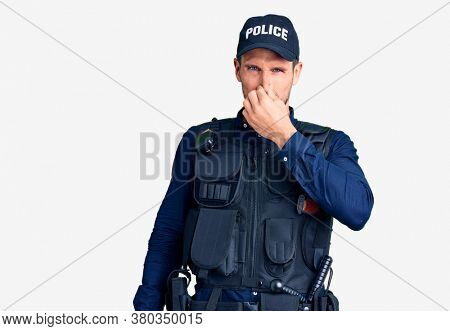 Young handsome man wearing police uniform smelling something stinky and disgusting, intolerable smell, holding breath with fingers on nose. bad smell