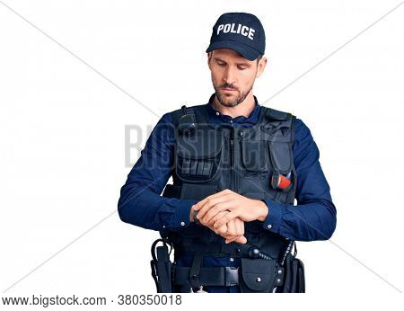Young handsome man wearing police uniform checking the time on wrist watch, relaxed and confident