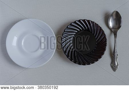 Black And White Saucers With A Spoon On A Light Table. Three Different Cutlery. Serving Option. View