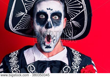 Young man wearing mexican day of the dead costume over red background scared and amazed with open mouth for surprise, disbelief face