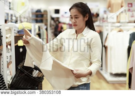 Women Looking Clothes In Shopping Mall. Asian Women Smileing Happy To Choice And Tried Clothes In Sh