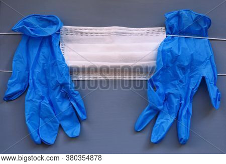 Pair Of Medical Blue Latex Protective Glove And White Mask On Gray Background. Protection Equipment