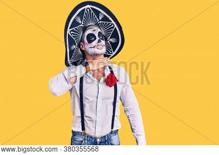 Man wearing day of the dead costume over background cutting throat with hand as knife, threaten aggression with furious violence