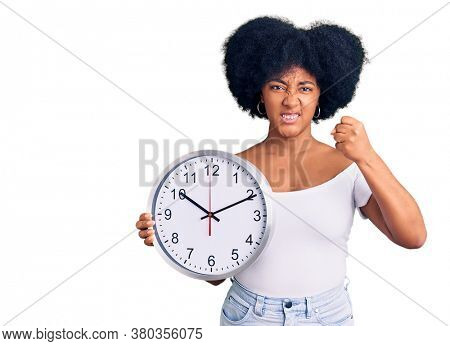 Young african american girl holding big clock annoyed and frustrated shouting with anger, yelling crazy with anger and hand raised