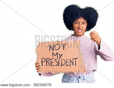 Young african american girl holding not my president protest banner annoyed and frustrated shouting with anger, yelling crazy with anger and hand raised