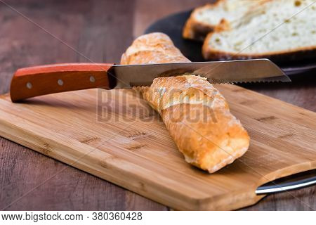 Bread Knife Stuck In A Loaf Of Bread On A Wooden Tray On A Wooden Table On An Out Of Focus Backgroun