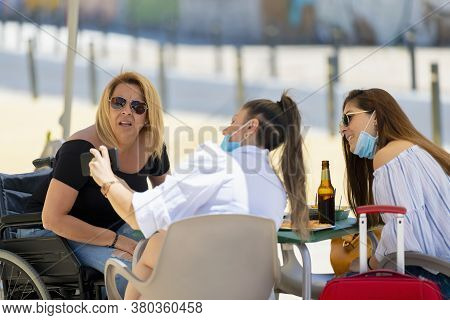 Women Using Surgical Masks Checking A Smart Phone While Having A Snack At An Outdoor Terrace On An O