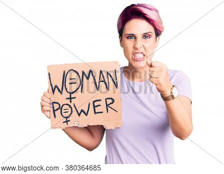Young beautiful woman with pink hair holding woman power banner annoyed and frustrated shouting with anger, yelling crazy with anger and hand raised