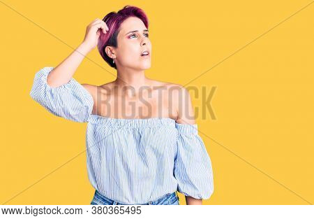 Young beautiful woman with pink hair wearing casual clothes confuse and wondering about question. uncertain with doubt, thinking with hand on head. pensive concept.