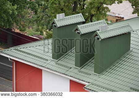 Green Metal Roof With Big Chimney Pipes And Ventilation System. White Rain Gutter.