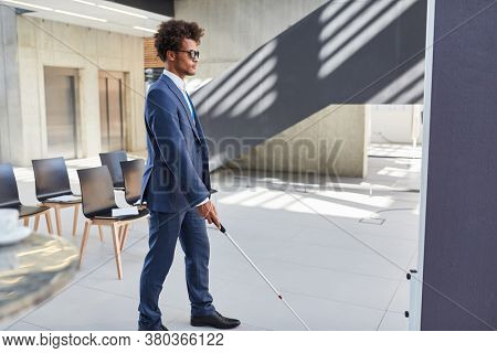 Blind African business man with cane at a meeting or congress