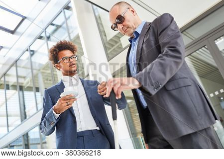 Blind man with a cane talking to an African businessman