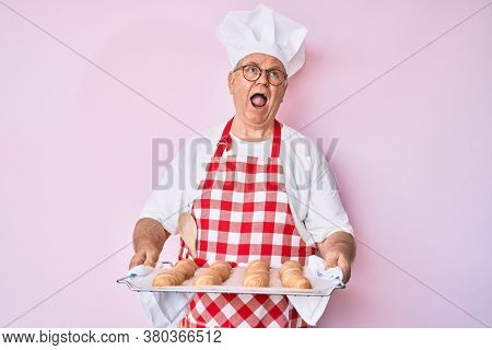 Senior grey-haired man wearing baker uniform holding homemade bread angry and mad screaming frustrated and furious, shouting with anger looking up.