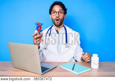 Handsome hispanic man wearing doctor uniform holding heart scared and amazed with open mouth for surprise, disbelief face