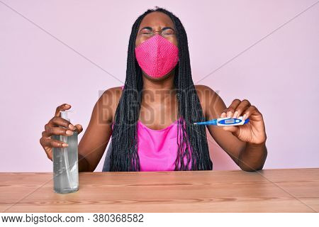 African american woman with braids wearing medical mask, hand sanitizer gel and thermometer angry and mad screaming frustrated and furious, shouting with anger looking up.