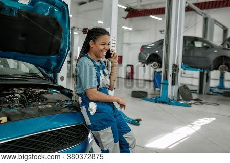 Young African American Woman, Professional Female Mechanic Talking On Phone, Leaning On Car With Ope