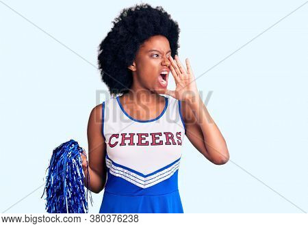 Young african american woman wearing cheerleader uniform holding pompom shouting and screaming loud to side with hand on mouth. communication concept.