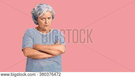 Senior woman with gray hair wearing casual striped clothes skeptic and nervous, disapproving expression on face with crossed arms. negative person.