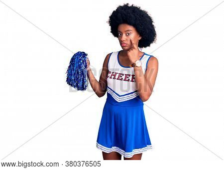 Young african american woman wearing cheerleader uniform holding pompom pointing to the eye watching you gesture, suspicious expression