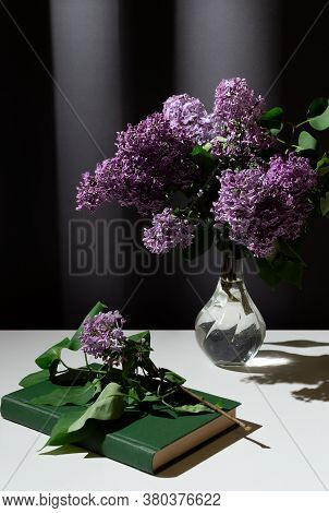 Still Life Of Bright Branch Of Lilac In The Glass Vase With Book On White Table On Grey Curtains Bac