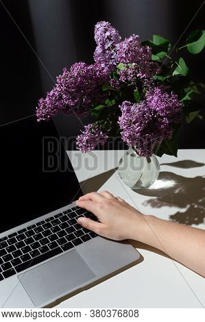 Still Life Of Bright Branch Of Lilac In The Glass Vase With Open Laptop And Hand On It On White Tabl