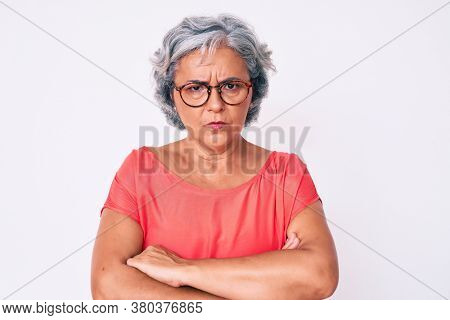 Senior hispanic grey- haired woman wearing casual clothes and glasses skeptic and nervous, disapproving expression on face with crossed arms. negative person.