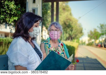 A Caregiving Nurse Reading A Book To An Elderly Patient While Sitting On A Street Bench. Both Are We