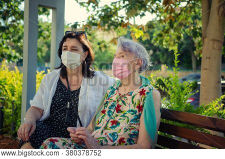 A Caregiver And Her Elderly Female Client, Wearing Protective Masks, Sit On A Park Bench Next To A H